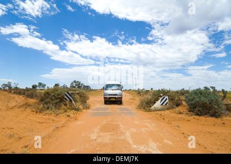 Aller sur une grille de bétail sur un chemin de terre dans une Toyota Hiace campervan, Mungo National Park, New South Wales, Australie