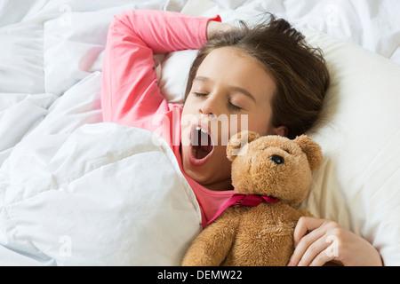 Jeune fille se réveillant yawning in bed Banque D'Images