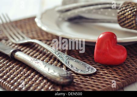 Plaque blanche, fourchette, couteau et coeur de pierre rouge sur fond de bois en osier libre. Focus sélectif. Banque D'Images