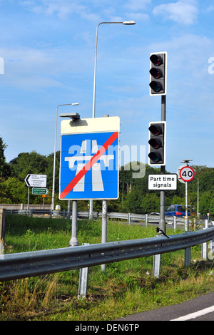 Un panneau routier indiquant la fin de l'autoroute à côté de feux de circulation.