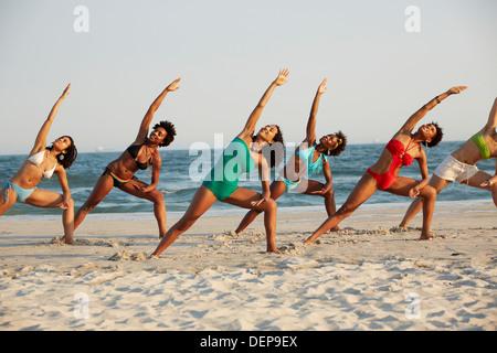 Women practicing yoga on beach