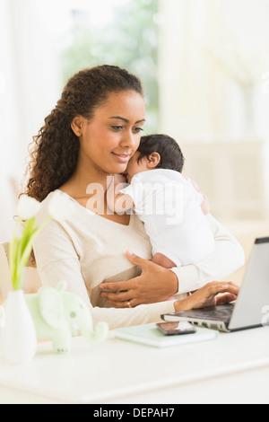 Ordinateur portable à l'aide de mère hispanique et tenant son fils mineur Banque D'Images
