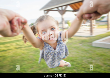 Woman spinning daughter in park Banque D'Images