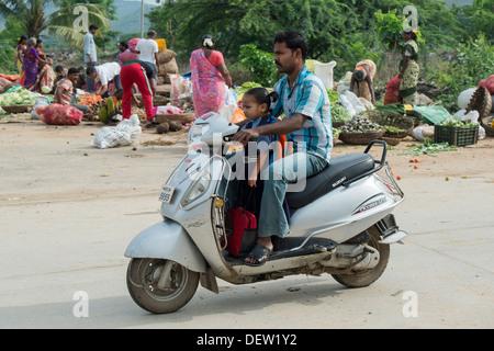 Prenant son père indien fille à l'école sur un cyclomoteur. L'Andhra Pradesh, Inde Banque D'Images