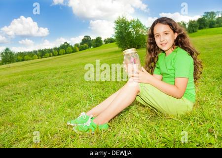 Happy little girl tenir pot avec papillon, assis sur le terrain dans le parc aux beaux jours d'été Banque D'Images