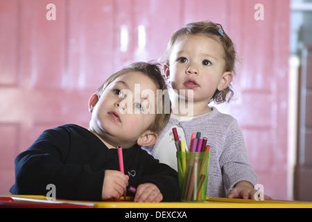 Frère et soeur 3 et 1, du dessin à un bureau, à l'appareil photo Banque D'Images