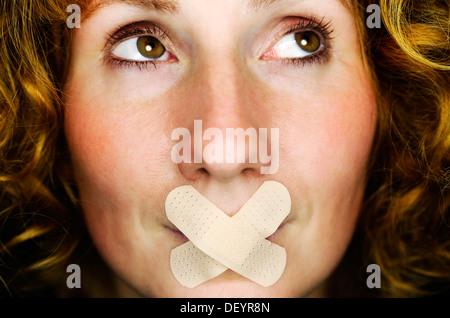 Femme avec ruban adhésif sur sa bouche, pour l'image symbolique de la parole interdite Banque D'Images