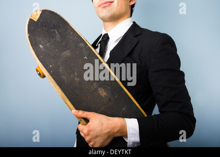 Jeune homme d'affaires à la recherche et de suffisance heureuse avec son skateboard
