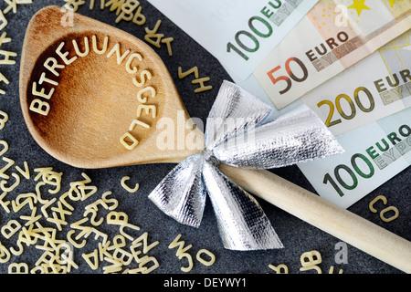 Cuillère en bois avec le mot Betreuungsgeld, Allemand pour les prestations de soignant, de lettres, de pâtes à côté Banque D'Images