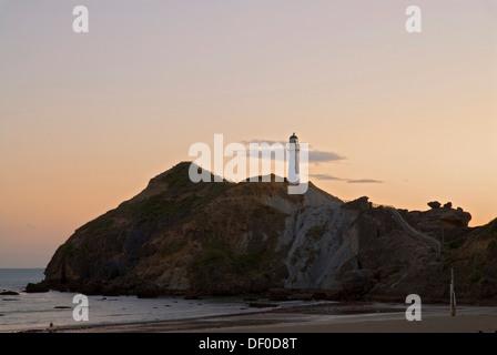 Lever du soleil derrière le phare à Castle Point et une piscine de marée à la côte Wairarapa, Nouvelle-Zélande Banque D'Images