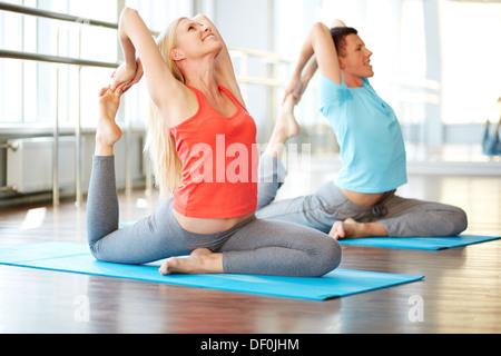 Portrait of happy young woman and man doing stretching de l'exercice dans la salle de sport Banque D'Images