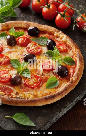 Pizza italien rustique avec de la mozzarella, fromage et de feuilles de basilic Banque D'Images