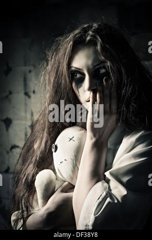 Style horreur shot: une étrange jeune fille triste avec moppet poupée dans les mains Banque D'Images