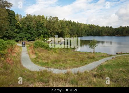 Gens touristes visiteurs marchant autour de Tarn Hows en été Cumbria Lake District National Park Angleterre Royaume-Uni GB Great Grande-Bretagne