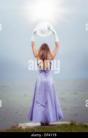 Une femme dans une robe pourpre est debout à un lac avec un chapeau de soleil Banque D'Images