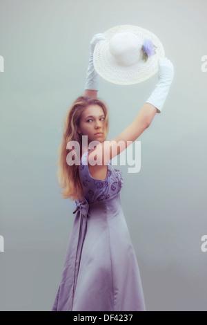 Une belle femme avec de longs cheveux blonds portant des gants et un chapeau de soleil Banque D'Images