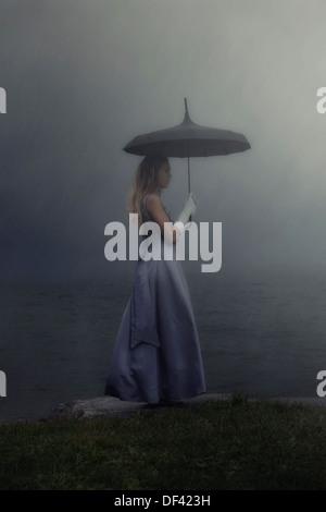 Une femme dans une robe pourpre est debout à un lac avec un parapluie noir sous la pluie Banque D'Images