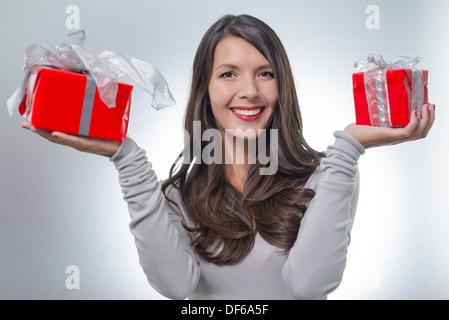 Jolie jeune femme aux longs cheveux brun et un beau sourire doux holding out rouge coloré des cadeaux pour un être Banque D'Images