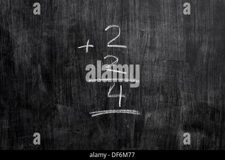 L'équation mathématique simple écrit avec la craie sur tableau noir Banque D'Images
