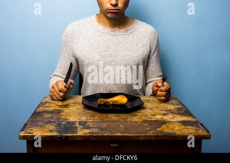 Jeune homme mange une pilons de poulet Banque D'Images