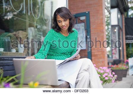 Propriétaire de petite entreprise travaillant sur ordinateur portable en dehors de cafe Banque D'Images