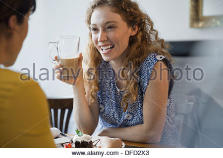 Female friends laughing at restaurant table Banque D'Images