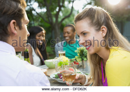 Heureux couple having meal with friends in backyard Banque D'Images