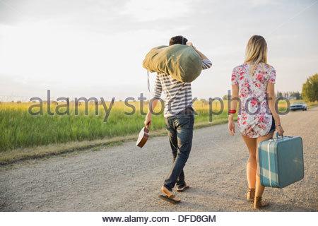 Vue arrière du jeune couple on country road Banque D'Images