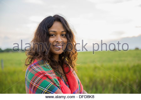 Portrait of smiling woman wrapped in blanket outdoors Banque D'Images