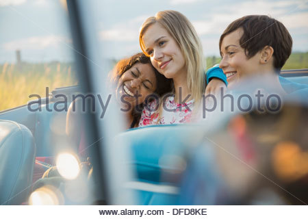 Young female friends sitting in convertible Banque D'Images
