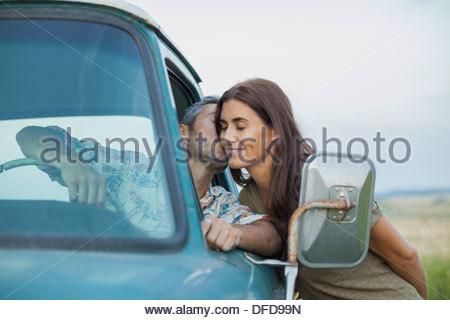 Affectueux baisers homme femme à travers la vitre du camion pick-up Banque D'Images