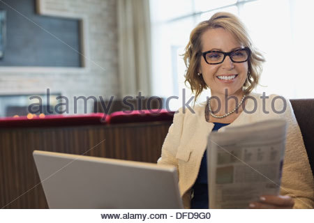Smiling businesswoman reading newspaper in hotel lobby Banque D'Images