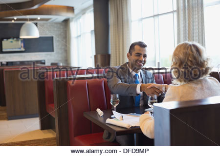 Business people shaking hands at hotel restaurant table Banque D'Images