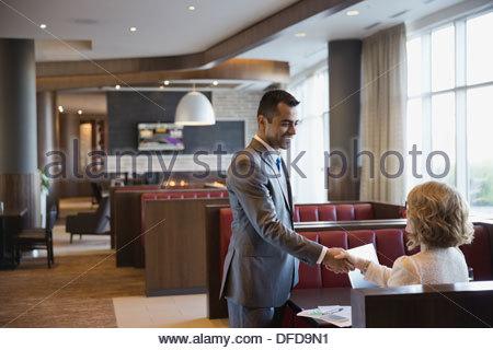 Businessman shaking hands with female colleague dans l''hôtel restaurant Banque D'Images