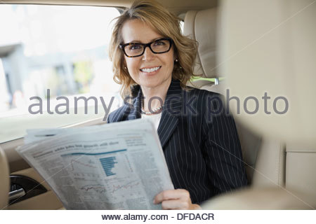 Portrait of businesswoman with newspaper sitting in car Banque D'Images