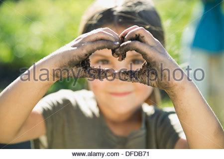 Petite fille en forme de coeur avec les mains couvertes de terre Banque D'Images