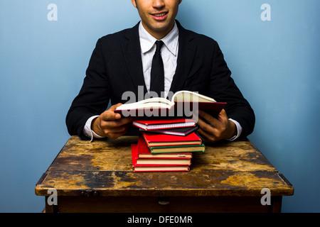 Jeune homme d'affaires est assis à un vieux bureau et lire un tas de livres Banque D'Images