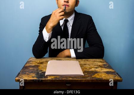 Homme d'affaires est assis à un bureau et penser Banque D'Images