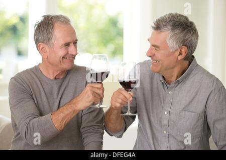 Senior men toasting wine glasses Banque D'Images