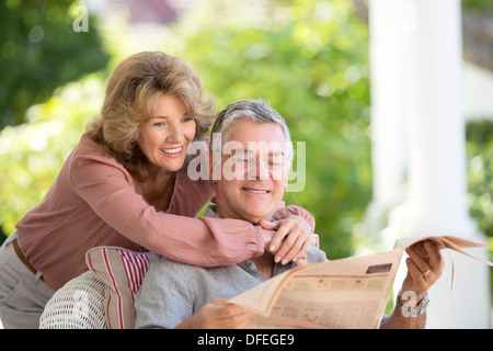 Senior couple reading newspaper on patio Banque D'Images