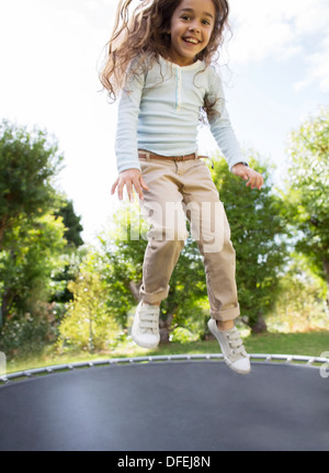 Girl jumping on trampoline en plein air Banque D'Images