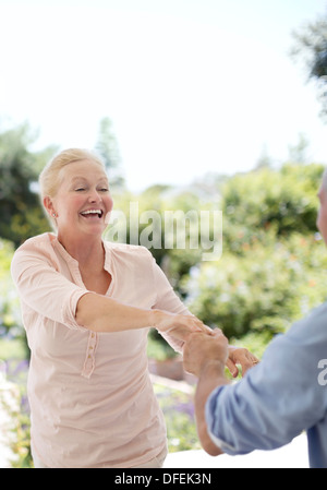 Senior couple dancing on patio Banque D'Images