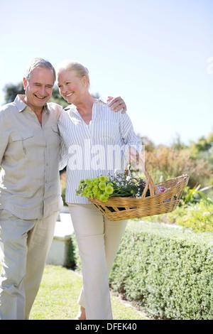 Couple dans jardin avec panier de fleurs