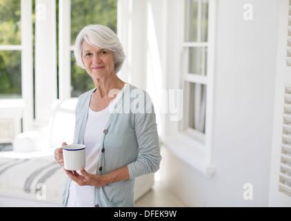 Senior woman holding tasse de café dans la chambre soleil Banque D'Images