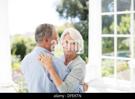Senior couple dancing on patio Banque D'Images