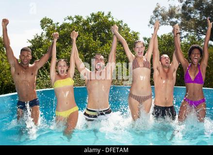 Amis jouant dans une piscine Banque D'Images