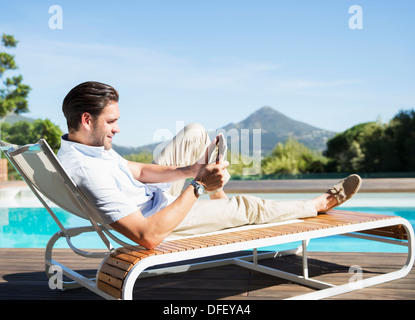 Man using digital tablet on lounge chair at poolside Banque D'Images