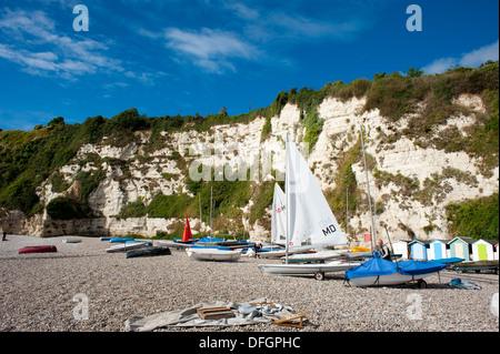 Bateaux à voile sur la plage de galets sous les falaises blanches de la bière à Devon, Angleterre Royaume-uni Banque D'Images