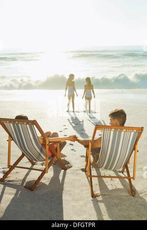 Les parents à regarder les filles sur la plage au coucher du soleil Banque D'Images