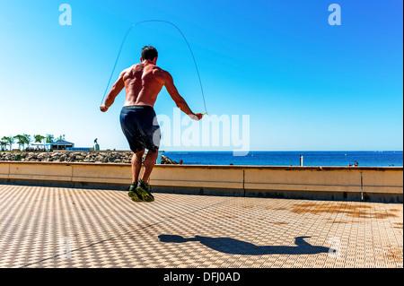 Europe, France, Alpes-Maritimes, Menton. Jeune athlète homme rendant le saut à la corde. Banque D'Images
